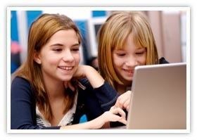 Two pre-teen girls practicing online research in a class